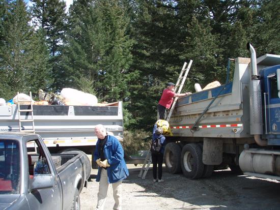 """Voluntários doam horas de trabalho e caminhões para evacuar o lixo coletado durante a limpeza anual de praia na Ilha Quadra. Esta limpeza anual é uma das centenas conduzidas em vias aquáticas do Canadá durante a Campanha """"Clean Sweep"""": Operação anual PITCH-IN do Canadá."""