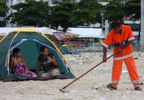 Gari trabalha aos olhos de pessoas que acamparam na praia após a festa Foto: Vitor Silva