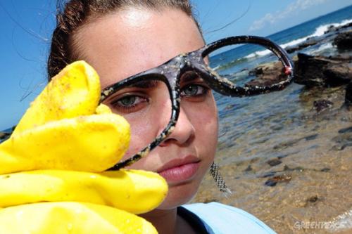 Voluntária realiza limpeza de praia em Salvador. ©Greenpeace/Lunaé Parracho